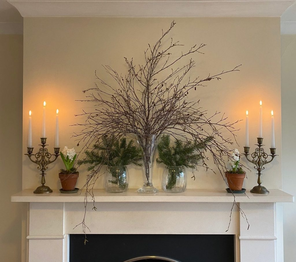 Fireplace decorated for winter with candles and greenery.